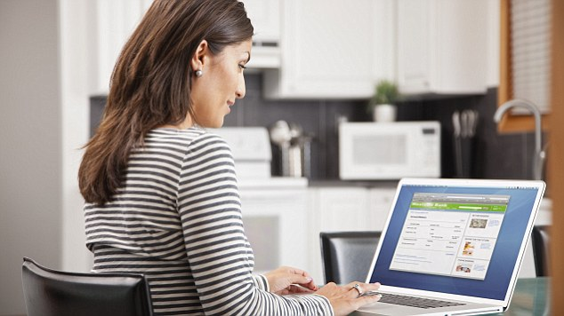 06 Jun 2012 --- Mature woman using laptop in kitchen --- Image by © VStock/Tetra Images/Corbis