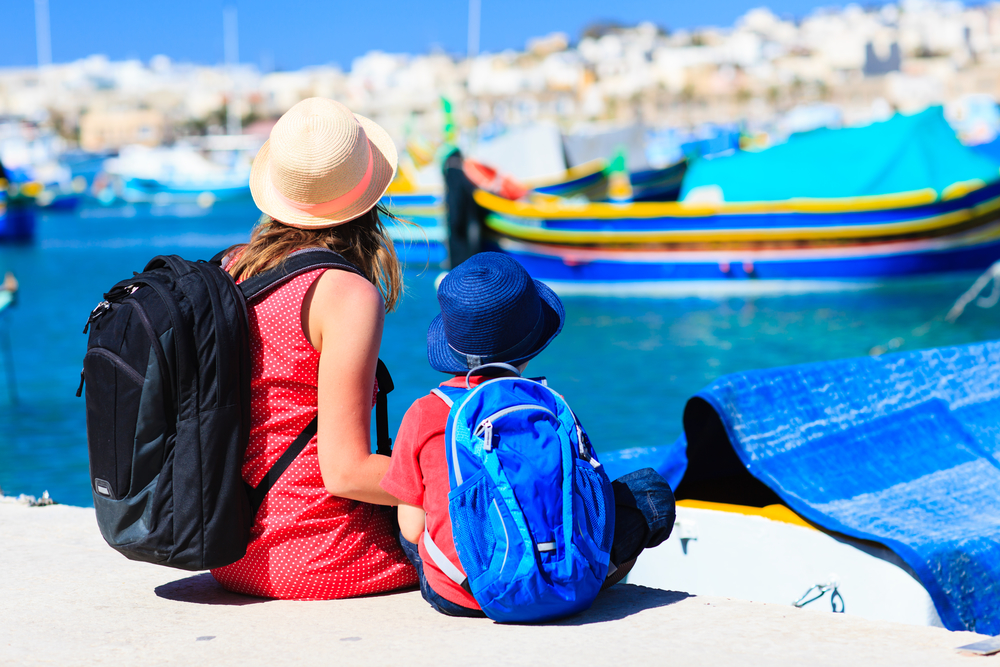 mother and son looking at traditional boats in Malta