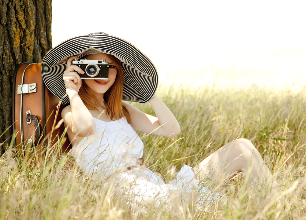 Redhead girl sitting near tree with vintage camera.